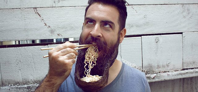 man eating noodles out of his beard with chopsticks