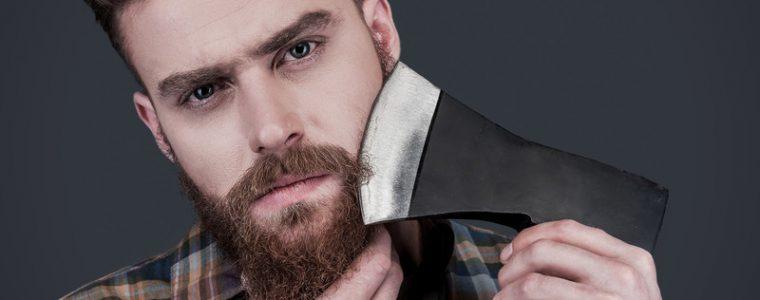 man shaving his face with a sharp axe